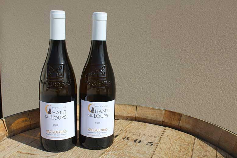 bouteilles du vacqueyras blanc bio sur une barrique de vin